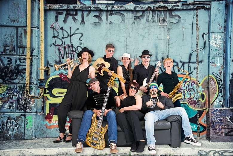 2FOUR2: Foto der Bandmitglieder vor einer Grafittiwand